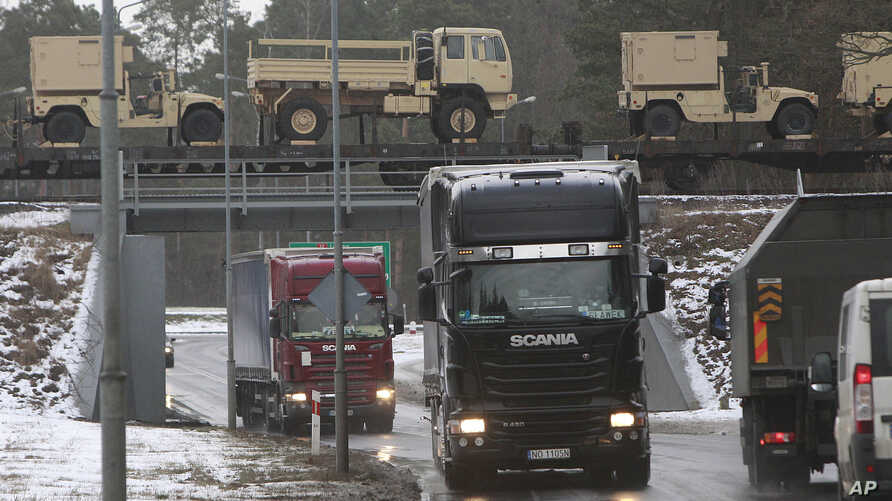American military vehicles are transported by train cross a bridge in Zagan, Poland, Jan. 12, 2017.