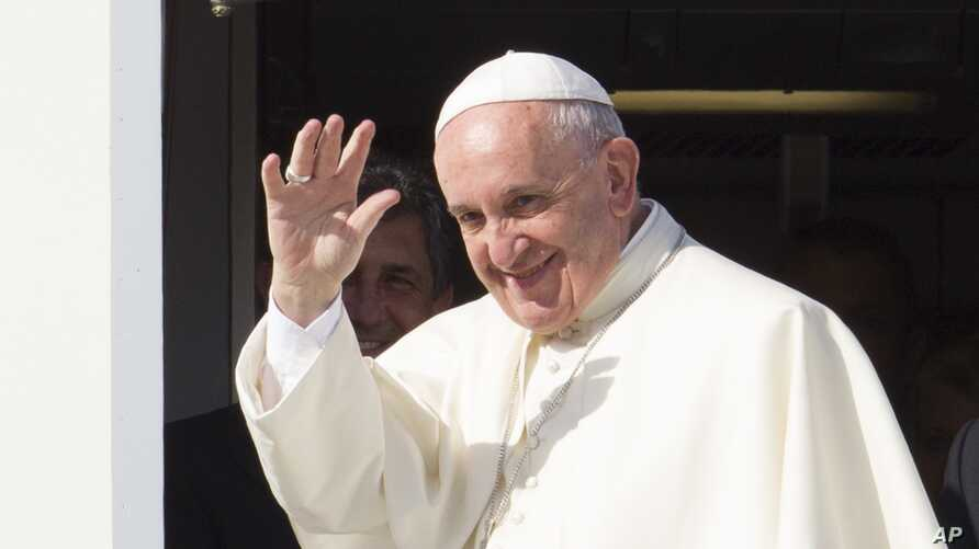 Pope Francis waves to reporters at Rome's Fiumicino international airport, Saturday, Sept. 19, 2015, as he boards his flight to Habana, Cuba, where he will start a 10-day trip including the United States.