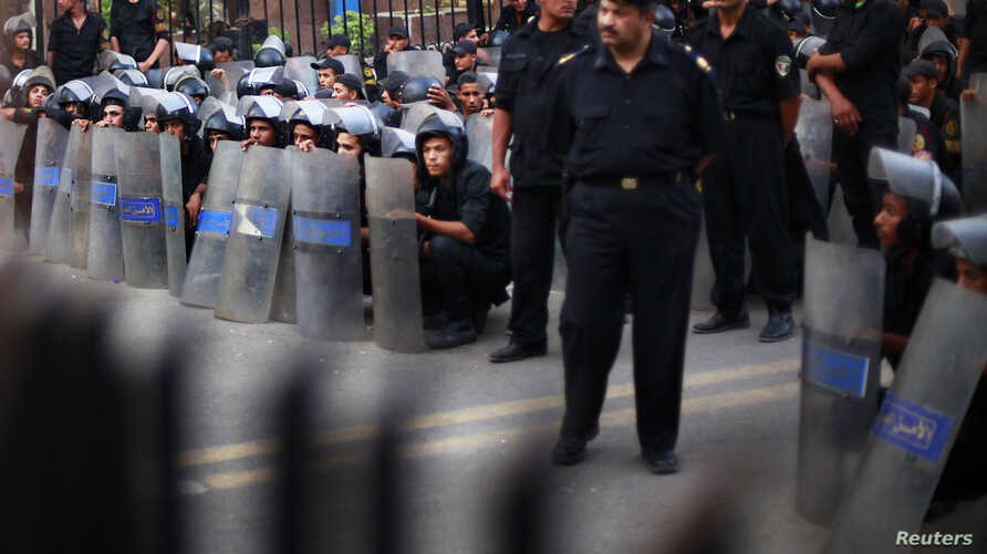 Police stand guard during a protest against the military council outside Egypt's parliament in Cairo, June 19, 2012.