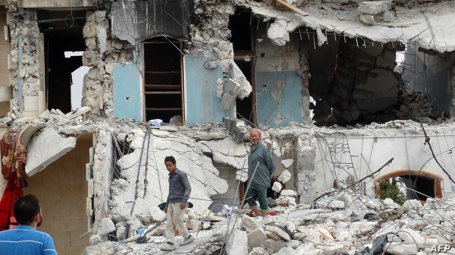 Syrians inspect the damage following a reported US-led coalition air strike against the headquarters of al-Nusra Front, 20 km west of the northern city of Aleppo on Sept. 25, 2014.