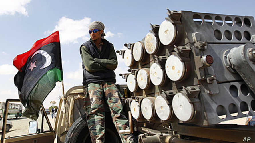 A rebel fighter stands on the back of a pick-up truck mounted with a rocket launcher at a staging post on the road between Ajdabiyah and Brega in Libya, April 9, 2011