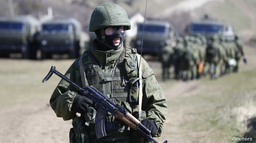 An armed man, believed to be a Russian soldier, stands on guard outside a military base in Perevalnoye, near the Crimean city of Simferopol, March 21, 2014.