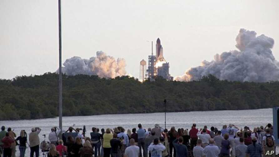 Media capture the launch of space shuttle Endeavour on the STS-134 mission to the International Space Station from the Press Site at NASA's Kennedy Space Center in Florida. The shuttle and its six-member crew lifted off on time at 8:56 a.m. EDT on Ma