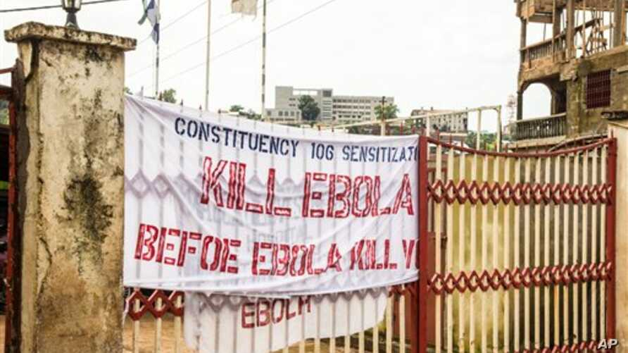 In this photo taken on Sunday, Sept. 14, 2014, a sign reading 'Kill Ebola Before Ebola Kill You', on a gate forming part of the country's Ebola awareness campaign in the city of  Freetown, Sierra Leone.  Shoppers crowded streets and markets in Sierra