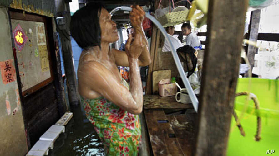 A Thai woman takes a shower in a narrow alley in a flooded neighborhood in Bangkok, Thailand, November 8, 2011.