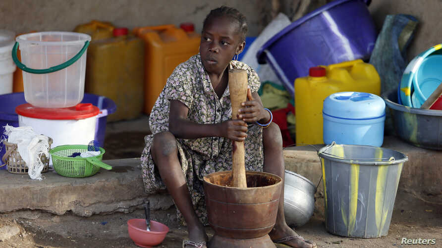 FILE - A girl displaced as a result of Boko Haram attacks in the northeast region of Nigeria, uses a mortar and pestle at a camp for internally displaced people in Yola, Adamawa State, Jan. 14, 2015.