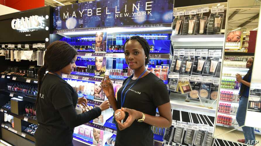 Sales assistants work at a Carrefour supermarket in Abidjan on Dec. 18, 2015 on opening day.