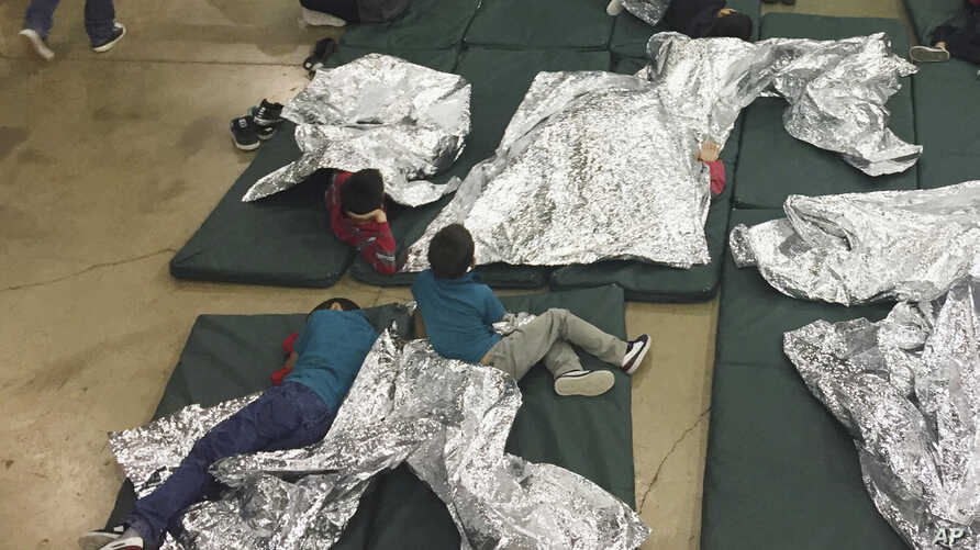 FILE - In this Sunday, June 17, 2018, file photo provided by U.S. Customs and Border Protection, people who've been taken into custody related to cases of illegal entry into the United States rest in one of the cages at a facility in McAllen, Texas.
