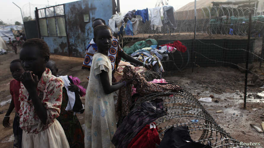 South Sudanese girls displaced by the fighting collect their laundry from a barbed wire in a camp for displaced persons in the UNMISS compound in Tongping in Juba February 19, 2014. Thousands of people have been killed and more than 800,000 have fled