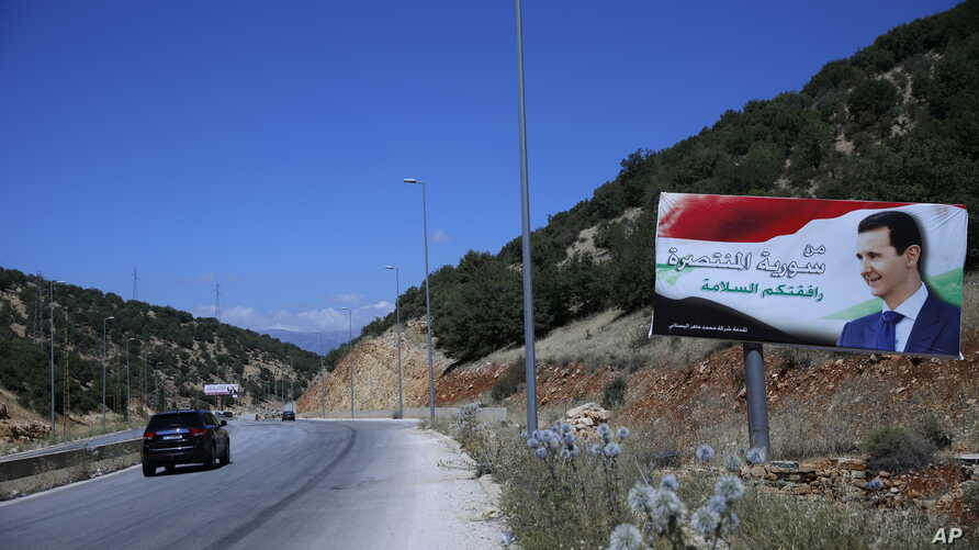 "In this Friday, July 20, 2018, photo, a poster of President Bashar Assad with Arabic that reads ""Welcome in victorious Syria."" is seen on the border between Lebanon and Syria."