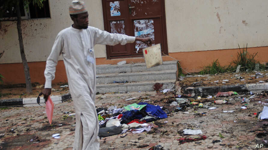 A man picks up an item belonging to a student at the site of a bomb blast in the university town of Zaria, Nigeria, July 7, 2015.
