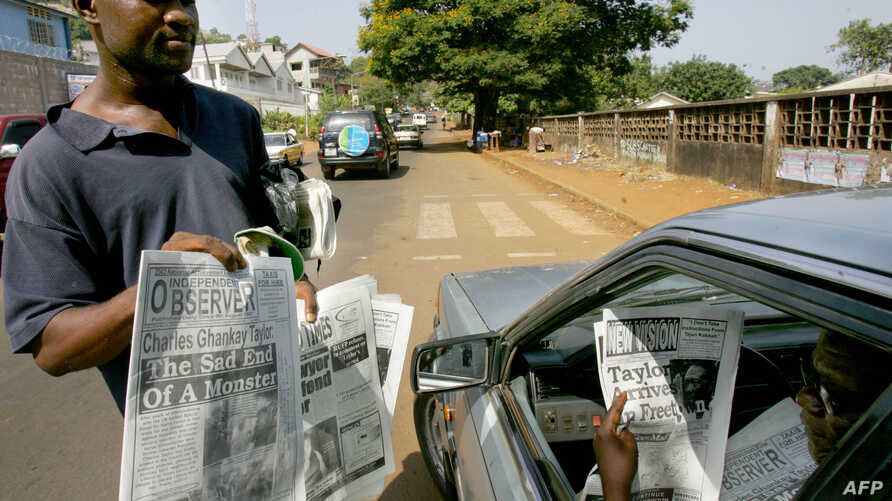 A man checks headlines of Sierra Leonean newspapers announcing 31 March 2006 in Freetown, where former Liberian President Charles Taylor, extradited from Nigeria to Monrovia 29 March 2006, has been indicted by the Special Court for Sierra Leone for c