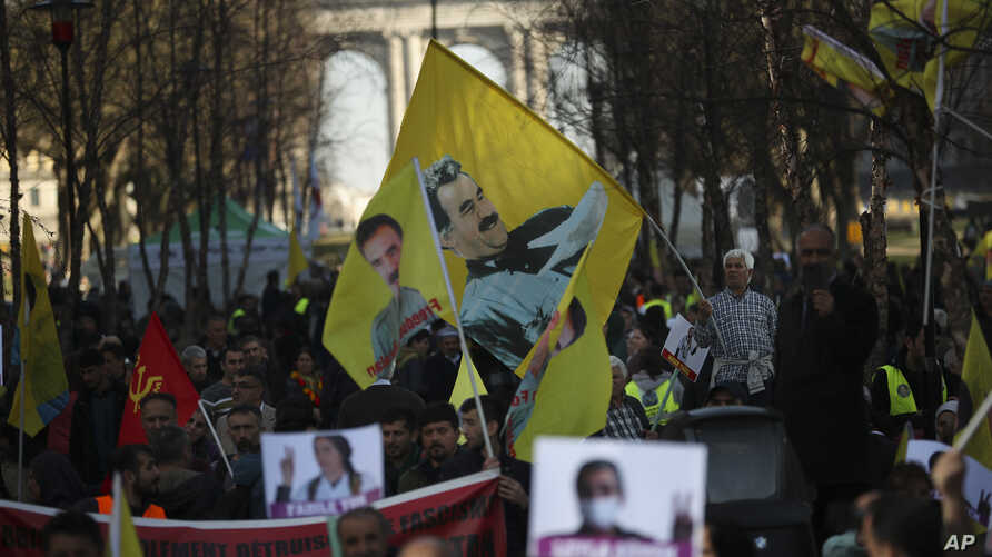 FILE - Pro-Kurdish people wave flags with the face of jailed Kurdistan Workers' Party, or PKK, leader Abdullah Ocalan during a protest demanding his freedom in Brussels, Feb. 27, 2019.