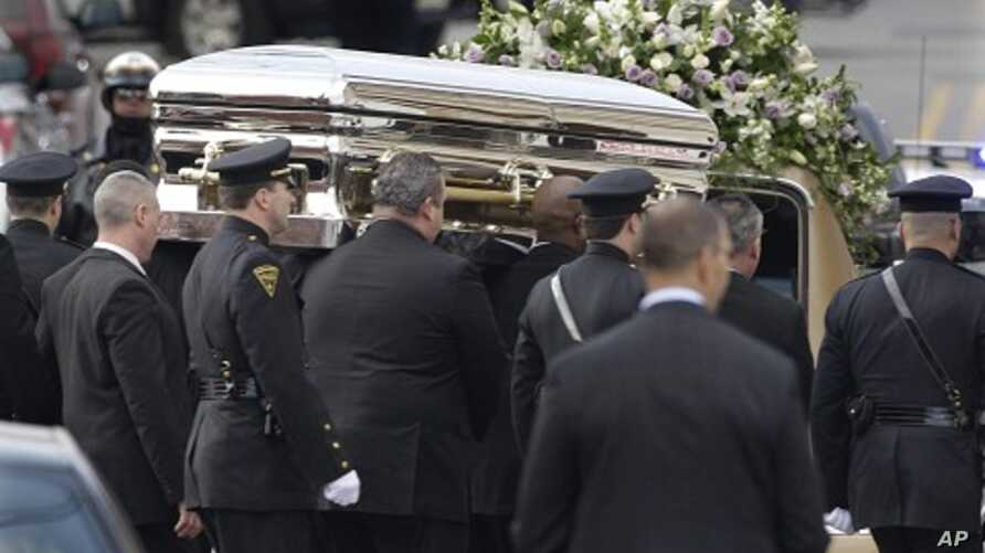 The coffin holding the remains of singer Whitney Houston is carried to a hearse after funeral services at the New Hope Baptist Church in Newark, N.J., February 18, 2012.