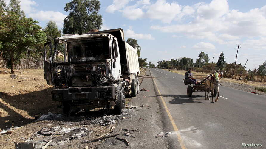 A man drives a horse-cart past the wreckage of a truck torched during recent demonstrations along the road in Holonkomi town, in Oromiya region of Ethiopia, Dec. 17, 2015.