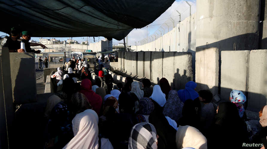 Israeli border police officers (L) stand guard as Palestinians wait to cross through the Qalandia checkpoint as they make their way to attend the first Friday prayer of the holy fasting month of Ramadan in Jerusalem's al-Aqsa mosque, near the West Ba