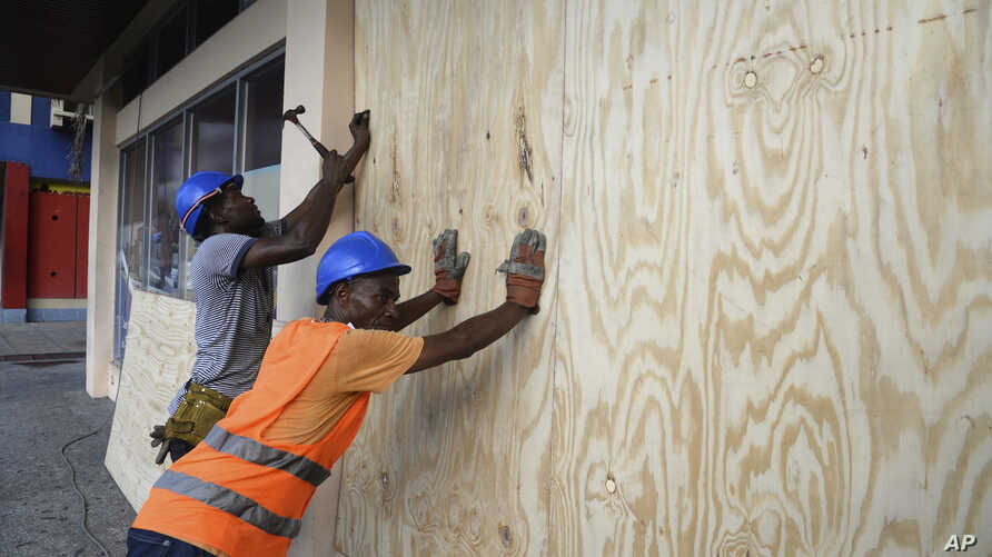 A worker nails a board to use on a storefront window as protection against hurricane Matthew in Kingston, Saturday, Oct. 1, 2016. One of the most powerful Atlantic hurricanes in recent history weakened a little on Saturday as it drenched coastal Colo...