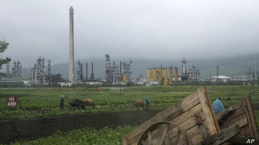 FILE - Farmers work their fields outside the Sungri Chemical Factory, an oil refinery in the Rason Special Economic Zone near North Korea's Russian and Chinese borders, July 23, 2016.