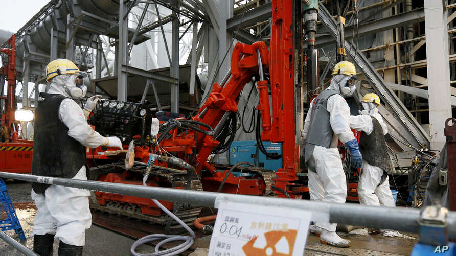 FILE - Workers drill pipes into the ground to be used to create a frozen underground wall to surround the crippled reactor buildings at Tokyo Electric Power Co.'s Fukushima Daiichi Nuclear Power Plant in Okuma, Fukushima Prefecture, northeast of Toky...
