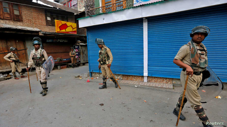 Indian policemen stand guard in front of the closed shops during a curfew in Srinagar, July 13, 2016.