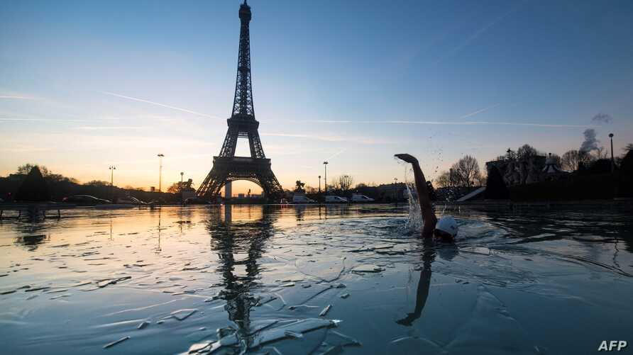 A man swims in the frozen water of the Trocadero fountain in front Eiffel Tower, Jan. 6, 2017, in Paris, France.