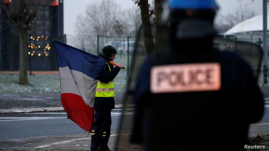 A protester wearing a yellow vest holds a French flag as the authorities dismantle their shelter at a traffic island near the A2 Paris-Brussels motorway in Fontaine-Notre-Dame, France, Dec. 14, 2018.