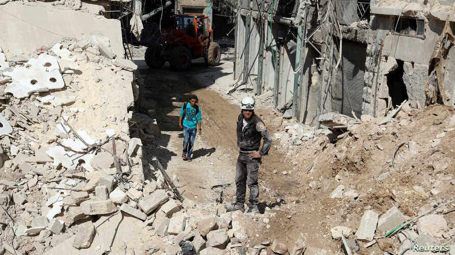 Civil defense members and men inspect a site damaged after an airstrike in the besieged rebel-held al-Qaterji neighborhood of Aleppo, Syria, Oct. 11, 2016.