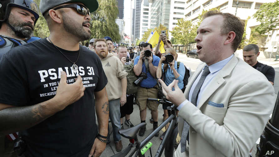 Joey Gibson, left, founder of the Patriot Prayer group, argues with a bystander at right as Gibson's group marched following a rally supporting gun rights, Aug. 18, 2018, at City Hall in Seattle.