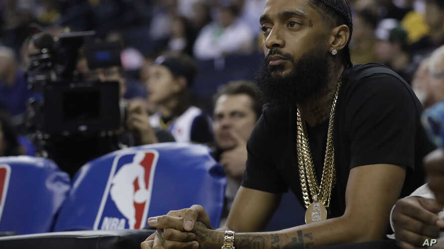 FILE - Rapper Nipsey Hussle watches an NBA basketball game between the Golden State Warriors and the Milwaukee Bucks, March 29, 2018, in Oakland, Calif.