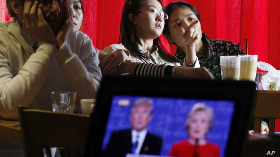 Chinese students chat as they watch a live broadcasting of the presidential debate between Democratic presidential nominee Hillary Clinton and Republican presidential nominee Donald Trump, at a cafe in Beijing, Sept. 27, 2016.