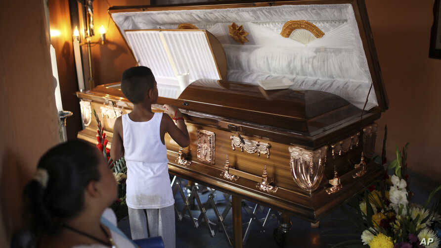 A boy looks at the coffin holding the body of Candido Rios Vazquez, a journalist for the Diario de Acayucan newspaper, who was murdered in Hueyapan de Ocampo in Veracruz state, Mexico, Aug. 23, 2017. Rios reportedly had been threatened repeatedly sin