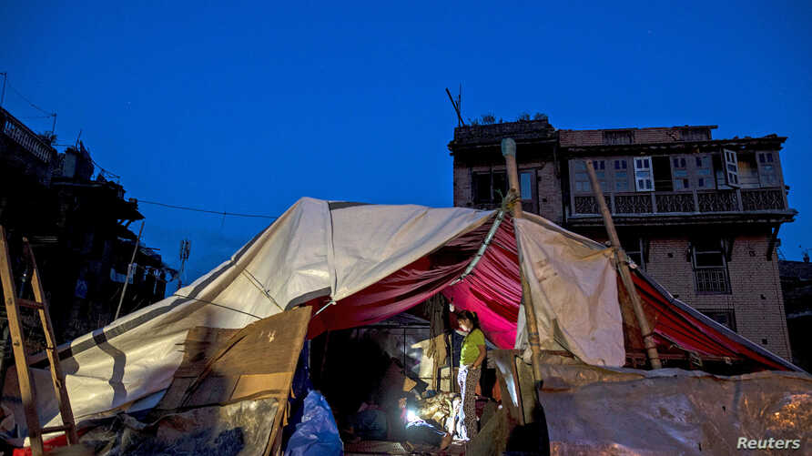 FILE - Local residents gather inside their temporary makeshift shelter after a fresh 7.3 earthquake struck, in Bhaktapur, Nepal, May 2015.