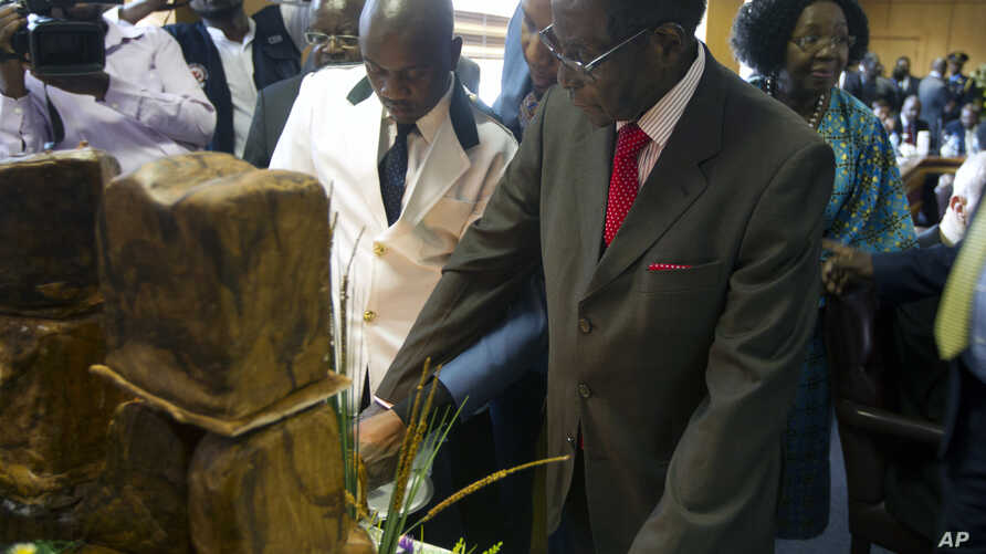 """Zimbabwe's President Robert Mugabe cuts his birthday cake as he marks his 93rd birthday at his offices in Harare, Tuesday, Feb. 21, 2017. Mugabe described his wife Grace, an increasingly political figure, as """"fireworks"""" in an interview marking his 93..."""