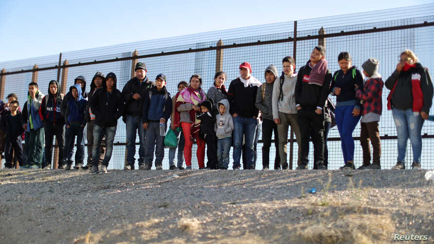 FILE - A group of Central American migrants surrenders to U.S. Border Patrol Agents south of the U.S.-Mexico border fence in El Paso, Texas, March 6, 2019.