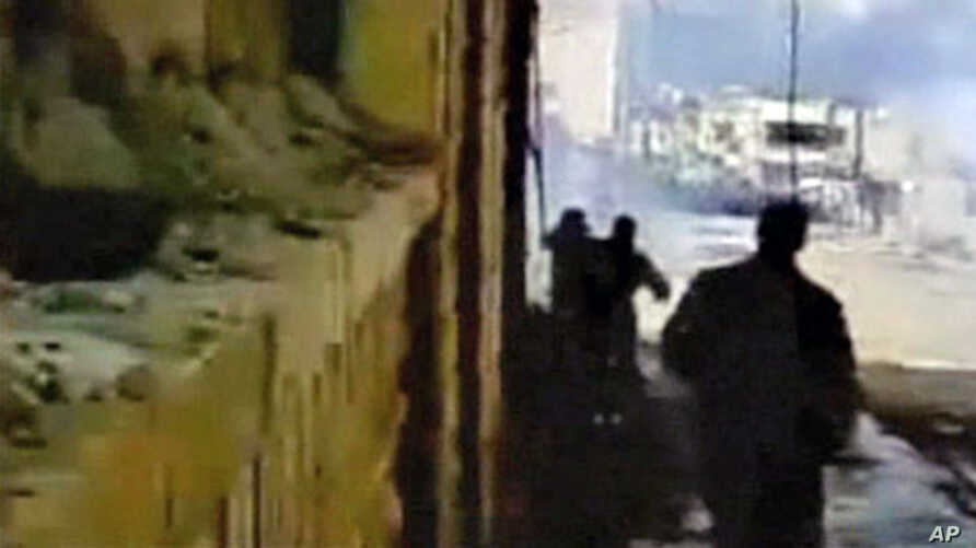 Protesters watch as tear gas fills a street during a demonstration in Deraa in this image from amateur video taken on Mar 23 2011 and posted on a social media website