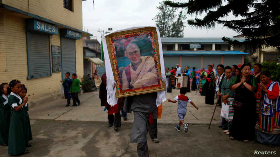 A Tibetan man carries a portrait of Dalai Lama during a function organised to mark the 82nd birthday celebration of Dalai Lama in Lalitpur, Nepal, July 6, 2017.
