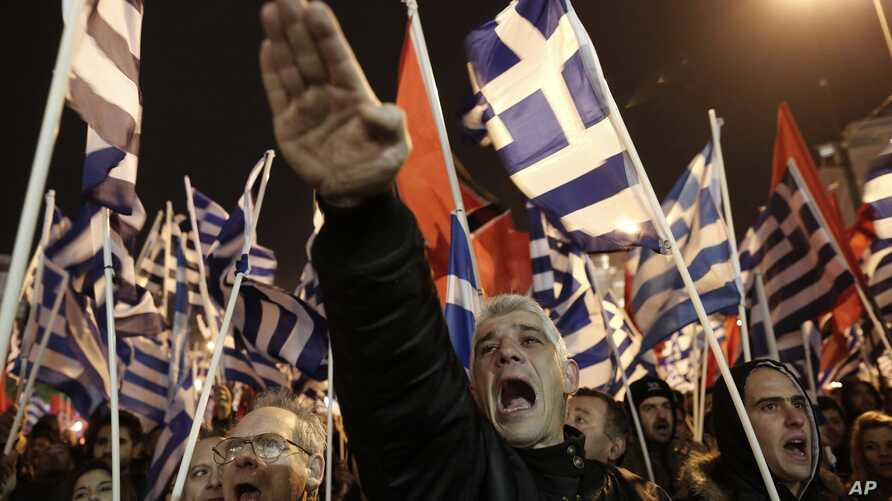 FILE - A supporter of Greece's extreme right Golden Dawn party raises his hand in a Nazi-style salute during a rally in Athens Feb. 1, 2014.