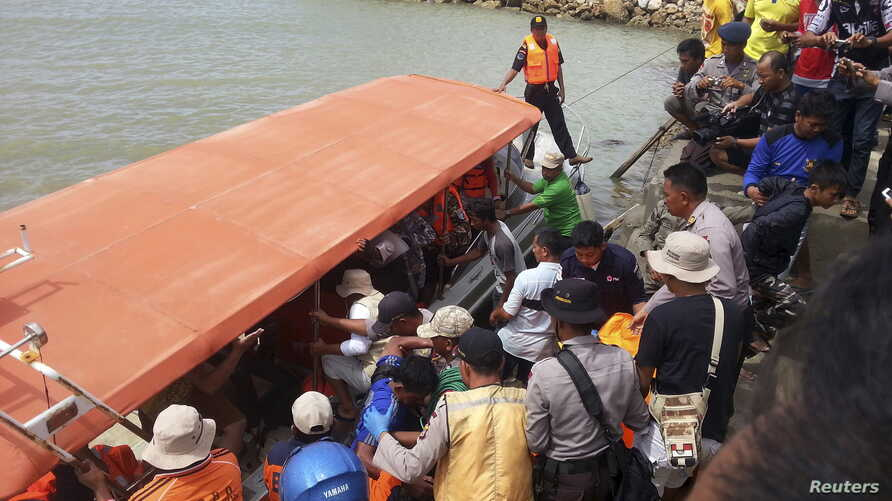 Rescue workers, police and residents prepare to unload the body of a ferry victim in Kolaka, South East Sulawesi, Indonesia, Dec. 20, 2015.