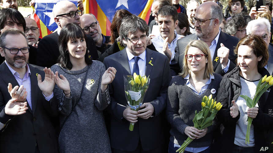 Former Catalan leader Carles Puigdemont, center, holds a bunch of flowers as he and supporters sing after a news conference in Berlin, Germany, Saturday, April 7, 2018.