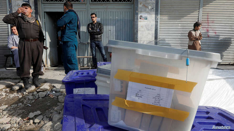 Afghan police officers stand guard while election commission workers prepare ballot boxes and election material at a polling station in Kabul, Afghanistan, Oct. 19, 2018.