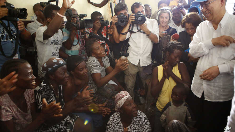U.N. Secretary-General Ban Ki-moon, right, speaks with women whose homes were destroyed by Hurricane Matthew, in a school where they have sought shelter in Les Cayes, Haiti, Oct. 15, 2016.