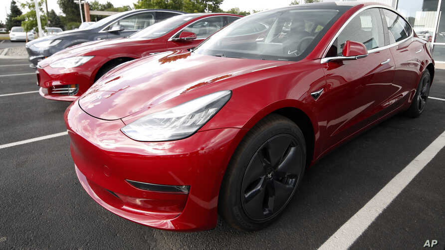 FILE - 2018 Model 3 sedans sit on display outside a Tesla showroom in Littleton, Colo., US.