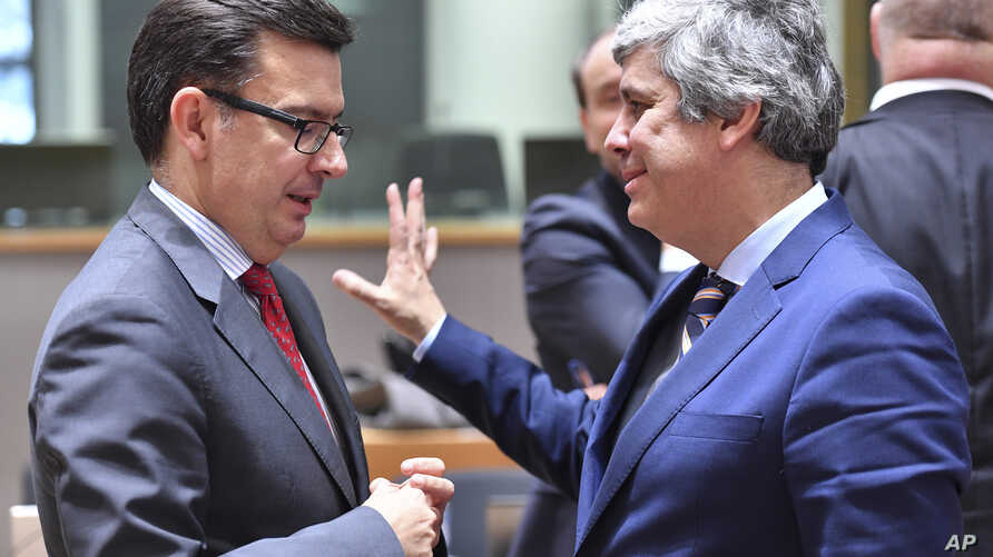 Portuguese Economy Minister and chief of the Eurogroup Mario Centeno, right, speaks with Spanish Economy, Industry and Competitiveness Minister, Roman Escolano during a meeting of the Eurogroup at the EU Council building in Brussels, March 12, 2018