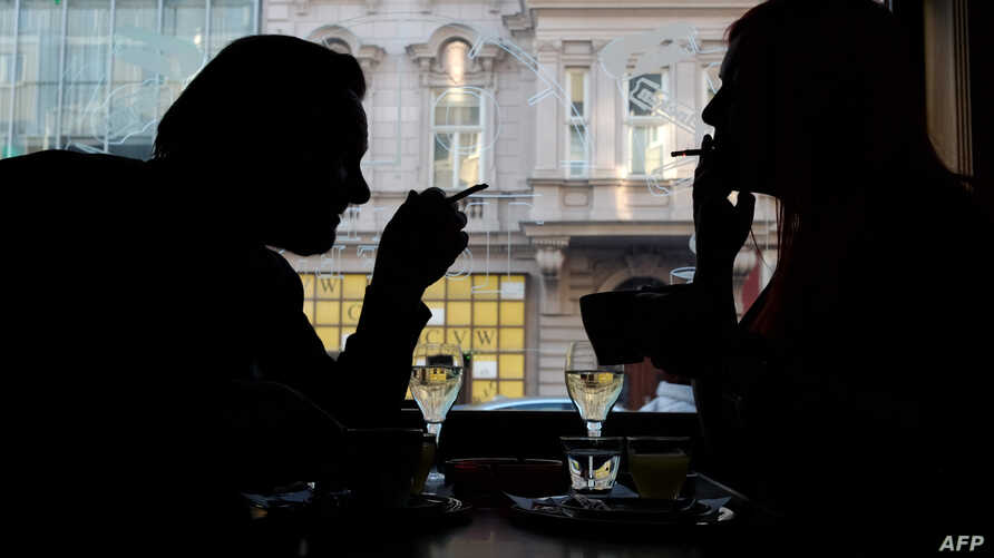 Guests of a Vienna's Cafe/Bar smoke cigarettes with their drinks in Vienna, Austria, on March 22, 2018.  Austrian MPs scrapped a smoking ban in bars and restaurants that was due to come into force in May, despite a petition in its favor collecting 54