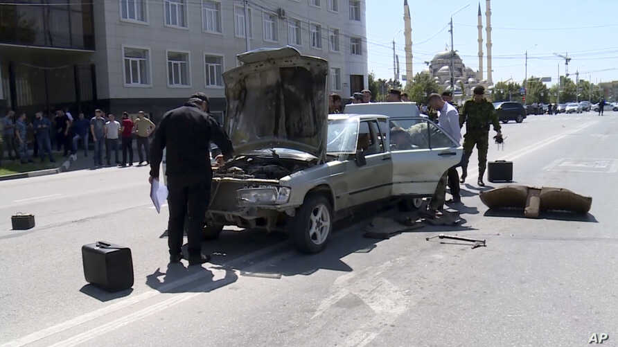 In this video grab provided by the RU-RTR Russian television, investigators inspect a car that was allegedly used to attack police in the regional capital, Grozny, Russia, Aug. 20, 2018.