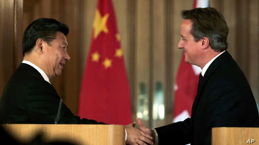 China's President Xi Jinping, left, shakes hands with Britain's Prime Minister David Cameron, during a joint press conference in 10 Downing Street, London, Oct. 21, 2015.