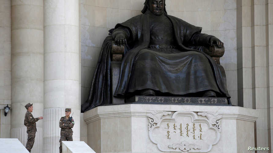FILE - Security personnel chat next to the statue of Genghis Khan at the parliament building in Ulaanbaatar, Mongolia, June 27, 2016.
