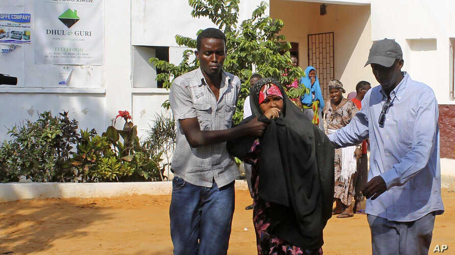 People assist a girl wounded in a suicide blast at popular restaurant in Mogadishu, November 3, 2012.