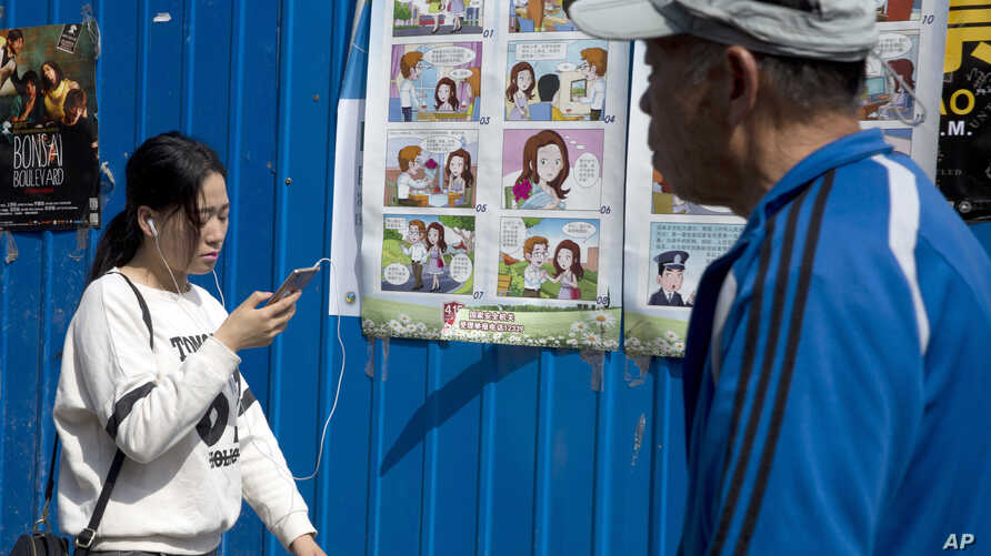 People walk past a poster warning against foreign spies in an alley in Beijing, China, April 20, 2016. China is marking National Security Education Day with the poster warning female government workers about dating foreigners, who could turn out to h