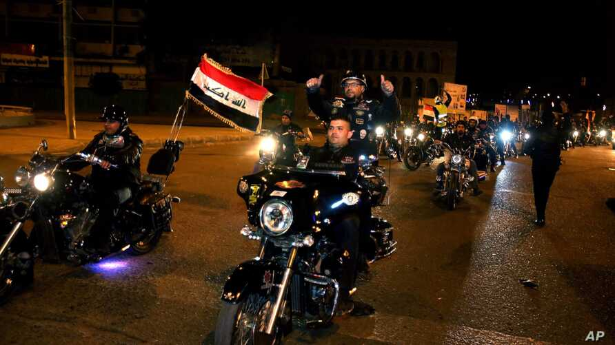 Iraqi bikers take part in a celebration after the lifting of the night-time curfew, at Tahrir Square in Baghdad, Feb. 5, 2015.